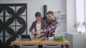 Ståenden av den lyckliga grabben med flickan i kök som ler kvinnan med mannen, förbereder sunt äta för lunch med nytt lager videofilmer
