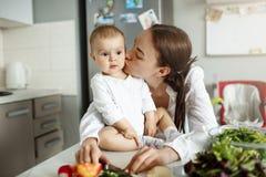 Ståenden av den lyckliga härliga modern som kysser hennes älskvärt, behandla som ett barn i kind i matställerum Behandla som ett  Fotografering för Bildbyråer