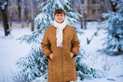 Ståenden av den lyckliga höga kvinnan som tycker om vinter, går royaltyfria foton