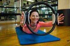 Ståenden av den lyckliga kvinnan som övar med pilates, ringer royaltyfria foton