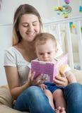 Ståenden av den lyckliga le läseboken för den unga kvinnan till hennes 10 gamla månader behandla som ett barn sonen Arkivbild