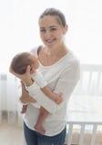 Ståenden av den lyckliga le modern som poserar med hennes litet, behandla som ett barn Arkivbilder