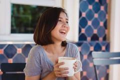 Ståenden av den lyckliga unga asiatiska affärskvinnan med rånar i händer som dricker kaffe i morgonen på kafét Arkivbild