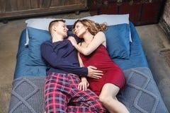 Ståenden av den lyckliga unga familjen har att vila i sovrum, i sleepwear som ligger på säng med den blåa sticka plädet som till  royaltyfri foto
