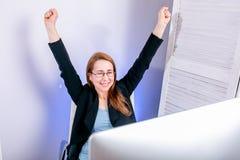 Ståenden av den lyckliga unga lyckade affärskvinnan firar något med armar upp på kontoret sinnesrörelsemodemodell som poserar pos arkivbilder