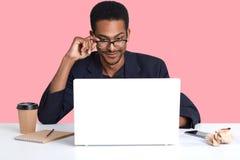 Ståenden av den mörka flådde mannen arbetar med bärbara datorn Den stiliga svarta mannen sitter på skrivbordet bär dräkten, tryck royaltyfria foton