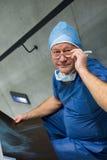 Ståenden av den manliga kirurgen undersöker röntgenstrålen på trappa Royaltyfria Bilder