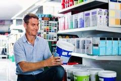 Ståenden av den manliga kunden som väljer målarfärg kan i housewaresdepa Arkivfoto