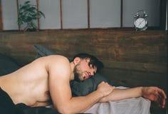 Ståenden av den manliga modellen för passformen i lyxigt sovrum badade sovande i ljust varmt morgonfönsterljus Royaltyfri Fotografi
