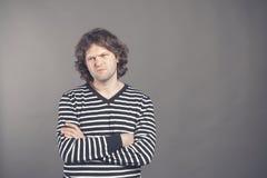 Ståenden av den missnöjda manliga modellen ser angrily med det vresiga uttryckt, uppehällen som armar korsade, bär den randiga tr arkivbild