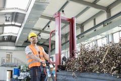 Ståenden av den mitt- vuxna arbetaren som drar handlastbilen, laddade med stålshavings i fabrik arkivbild