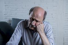 Ståenden av den mogna gamala mannen för pensionären på hans ledsna för soffa för 60-tal hemma ensamma känsliga och bekymrade lida Fotografering för Bildbyråer
