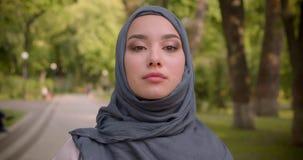 Ståenden av den muslim kvinnan i hijab med ljust utgör att hålla ögonen på fast beslutsamt in i kamera som går i, parkerar arkivfilmer