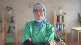 Ståenden av den muslim kvinnan i hijabdoktor tar bort förbinder att le och att se kameran lager videofilmer