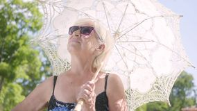 Ståenden av den positiva le mogna kvinnan i solglasögon som står i, parkerar under den vita slags solskydd som omkring ser och lager videofilmer