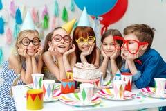 Ståenden av den roliga gruppen av barn bär partilock, stora anblickar, blick med stor aptit på födelsedagkakan, önskar till arkivfoton