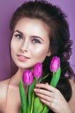 Ståenden av den romantiska unga kvinnan med tulpan blommar och makeup som ser kameran Vårmodefoto Royaltyfri Foto