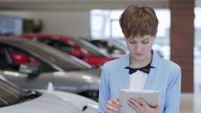 Ståenden av den säkra nätta kvinnan i formella kläder som använder hennes minnestavla, står framme av suddiga bilar i motorshow stock video