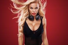 Ståenden av den sexiga discjockeyn med lyssnar musik på röd bakgrund med kopieringsutrymme Hår blåser vinden royaltyfri fotografi