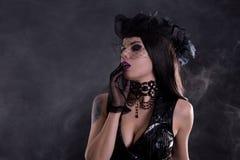 Ståenden av den sexiga gotiska flickan skyler in hatten Royaltyfria Foton