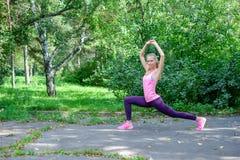 Ståenden av den sportiga kvinnan som gör sträckning, övar parkerar in, innan det utbildar Kvinnlig idrottsman nen som förbereder  royaltyfri foto