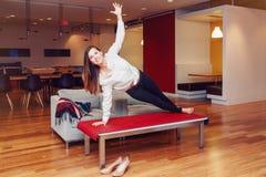 Ståenden av den sportiga unga vita Caucasian affärskvinnan för den slanka passformen som mediterar göra yoga, övar arkivbilder