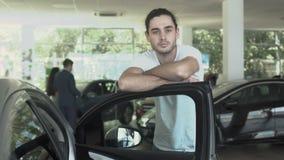 Ståenden av den stilfulla grabben lutar på dörr av den moderna automatiskn i bilåterförsäljare arkivfilmer