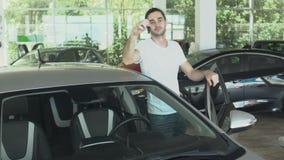 Ståenden av den stilfulla grabben lutar på dörren av bilen med biltangenter i bilåterförsäljare arkivfilmer