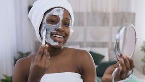 Ståenden av den stiliga afrikansk amerikankvinnan med handduken på huvudet som applicerar leramaskeringen på halvan av att använd arkivfilmer