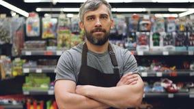 Ståenden av den stiliga skäggiga grabben erfor representanten i förklädeanseende i leksakavdelning i supermarket som ser lager videofilmer