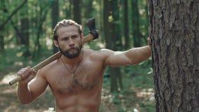 Ståenden av den stiliga skäggiga mannen går med yxa i skogen långsamt arkivfilmer
