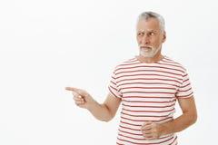 Ståenden av den tveksamma tvivelaktiga och missnöjda intensiva höga mannen som ser och pekar, lämnade misstänksamt med avoghet oc arkivfoto