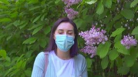 Ståenden av den unga allergiska kvinnan i medicinsk maskering nyser och ser kameran lager videofilmer