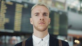 Ståenden av den unga attraktiva affärsmannen ser in i kameran på flygplatsen på avvikelse stiger ombord bakgrund, känner sig arkivfilmer