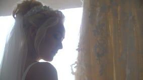 Ståenden av den unga attraktiva blonda bruden med charmigt leende som tycker om och, trycker på hennes långa stilfulla bröllopskl arkivfilmer