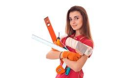 Ståenden av den unga attraktiva brunettbyggnadskvinnan i röd likformig med hjälpmedel i händer gör renovering och att se arkivbilder
