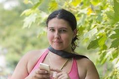 Ståenden av den unga attraktiva kvinnan med en mobiltelefon på sommargräsplan parkerar royaltyfri fotografi