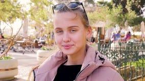 Ståenden av den unga blonda flickan med långt hår sitter i ett offentligt ställe i parkerar och ler på kameran från arkivfilmer