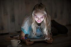 Ståenden av den unga blonda kvinnan ser och läser på minnestavlan och drickakaffe på natten flickan använder minnestavlan Arkivfoto