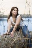 Ståenden av den unga brunettkvinnan parkerar in Härlig modell som poserar nära vattnet Modell plus format Arkivfoto