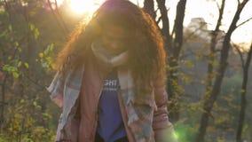 Ståenden av den unga caucasian lockig-haired kvinnan som går i soligt höstligt, parkerar och samlar dancingly sidor lager videofilmer