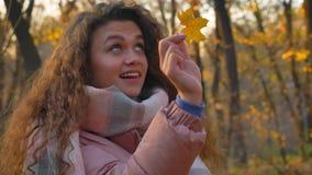 Ståenden av den unga caucasian lockig-haired kvinnan som undersöker det gula bladet och kastar det i soligt höstligt, parkerar stock video