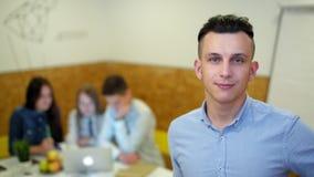 Ståenden av den unga chefen i kontoret med hans lag arbetar på projekt arkivfilmer