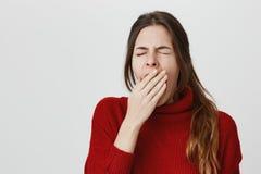 Ståenden av den unga gulliga trötta flickan som gäspar med hennes ögon, stängde sig och täcker hennes mun, över den vita väggen k arkivbild