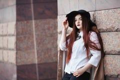 Ståenden av den unga härliga damen som bär den stilfulla klassikern, beklär att posera på gatan framåt se för flicka Plus formatm royaltyfri foto
