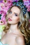 Ståenden av den unga härliga kvinnan med långt blont hår i eleganta blått klär att posera på blom- bakgrund Royaltyfri Foto