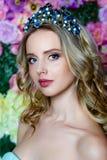 Ståenden av den unga härliga kvinnan med långt blont hår i eleganta blått klär att posera på blom- bakgrund Arkivfoton