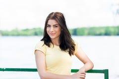 Ståenden av den unga härliga kvinnan mot sjön i sommarstad parkerar Arkivbild