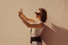 Ståenden av den unga härliga lockiga brunettflickan i solglasögon med röda kanter som talar telefonen, gör selfi Royaltyfri Foto