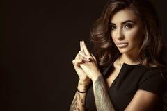 Ståenden av den unga härliga tatuerade kvinnan med frodigt glänsande krabbt hår och gör perfekt sminkinnehavhänder i skyttegest Royaltyfri Foto